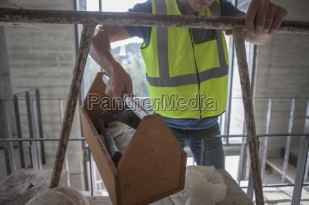 bauarbeiter traegt kisten auf baustelle