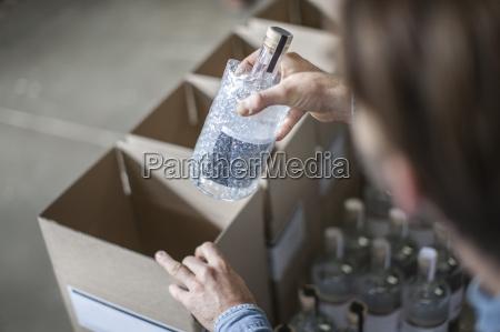 mann wirft flasche schnaps in karton