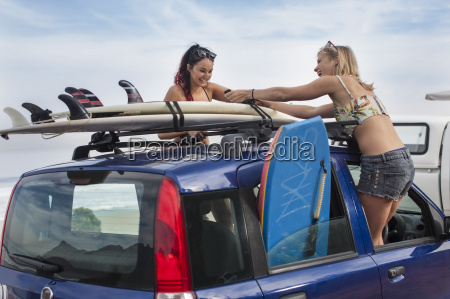 two happy young women unwrapping surfboards