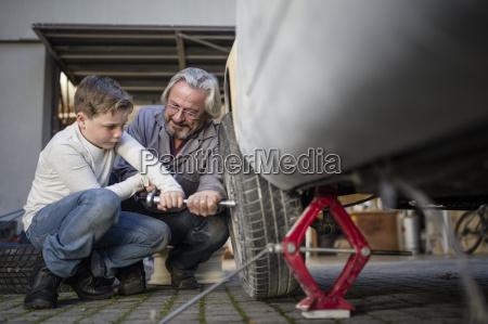senior man and boy changing car