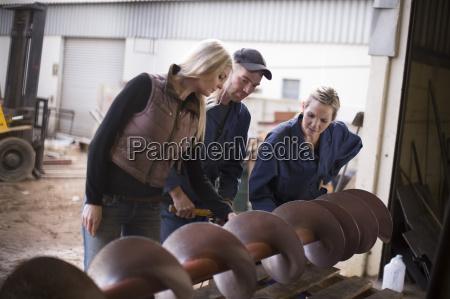 frau und zwei arbeiter inspektion maschine