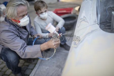 senior mann auf dem auto spritzen