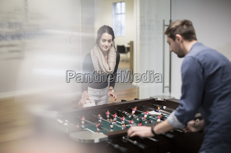 two colleagues playing foosball in office