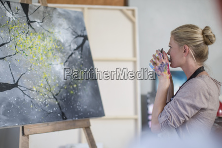 female painter drinking coffee in front