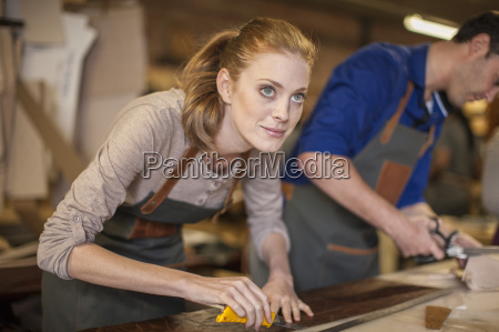 smiling woman working in leather workshop