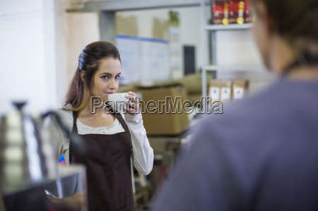 woman drinking coffee from cup looking