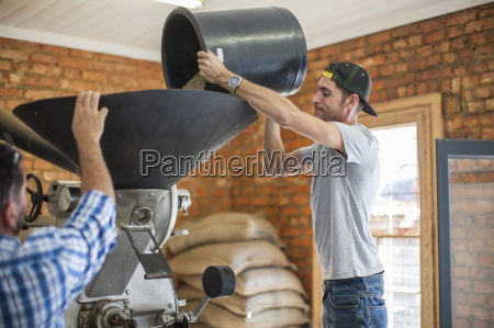 man pouring coffee beans into a