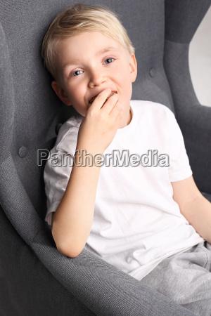portraet eines jungen auf einem stuhl