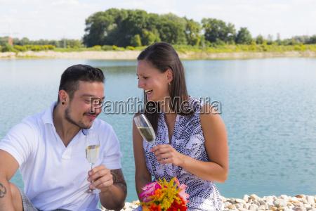glueckliches junges paar mit sektglaeser verlobung