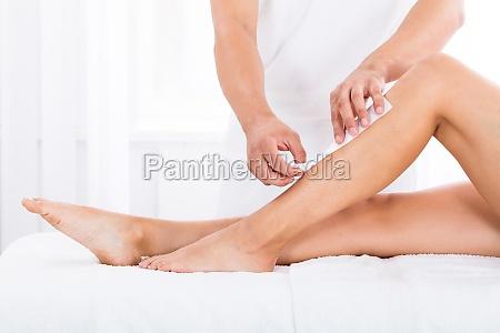beautician waxing womans leg