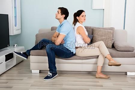 couple sitting back to back on