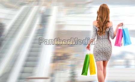 junge frau mit einkaufstaschen in einkaufszentrum