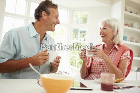 middle aged couple enjoying breakfast at