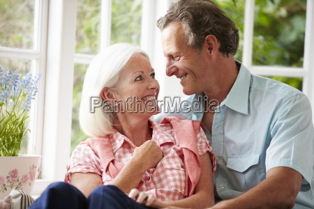 middle aged couple sitting on window