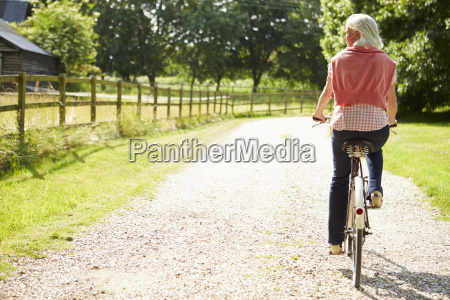 middle aged woman enjoying country cycle