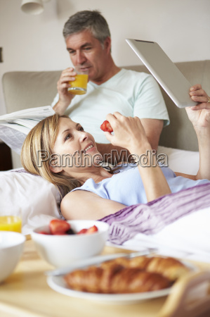 couple eating breakfast in bed with