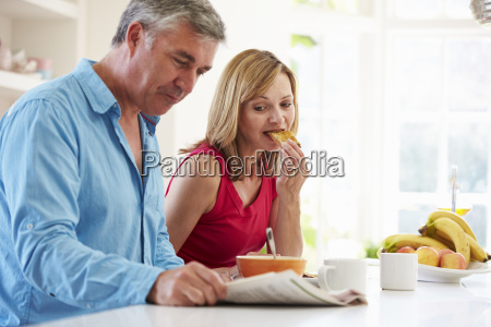 middle aged couple having breakfast in