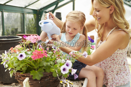 mother and daughter watering plants in