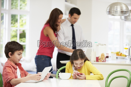 family using digital devices at breakfast