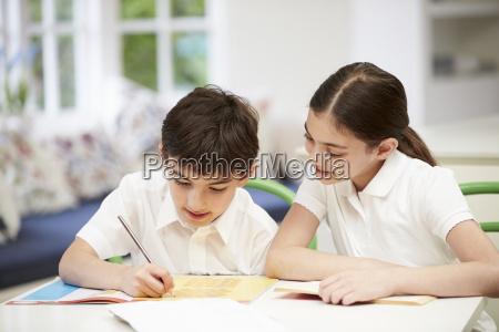 children wearing school uniform doing homework