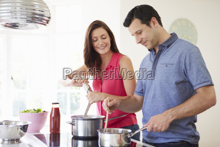 hispanic couple cooking meal at home
