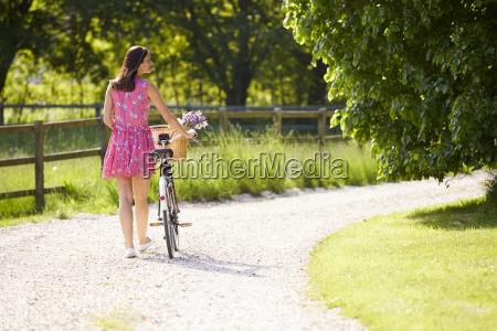 rear view as woman pushes bike