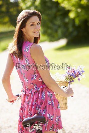 attractive woman pushing bike along country