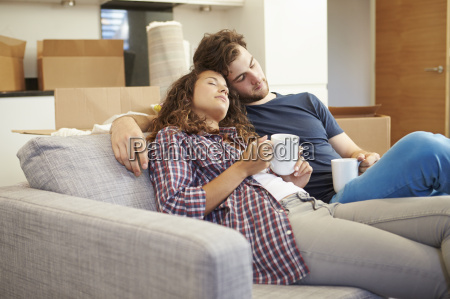 tired couple relaxing on sofa in