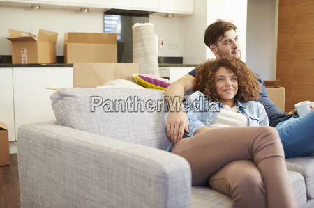 couple relaxing on sofa with hot