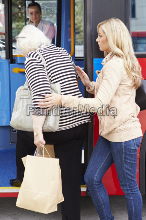 woman helping senior woman to board