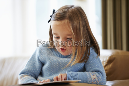 young girl reading story at home