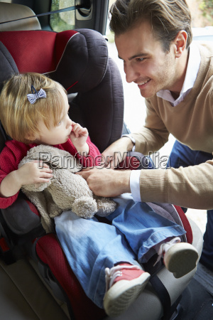 father putting young girl into car