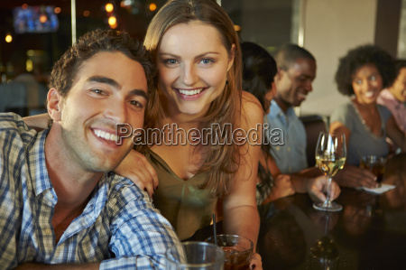 couple enjoying drink at bar with
