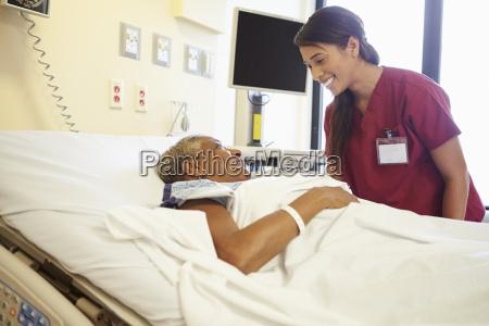 nurse talking to senior woman in