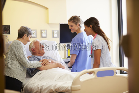 medical team meeting with senior couple