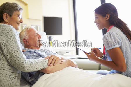 female doctor talking to senior couple