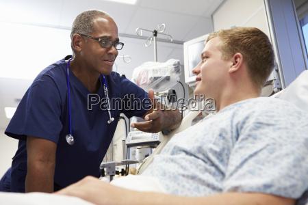 junge maennliche patienten maennliche krankenschwester reden