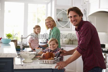 family preparing roast turkey meal in