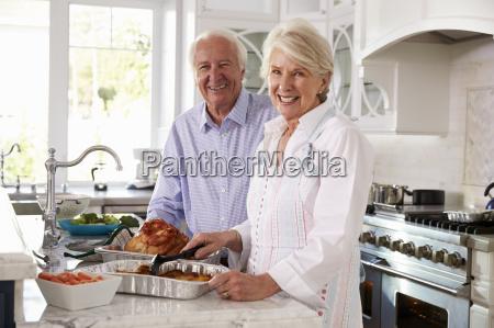 senior couple make roast turkey meal