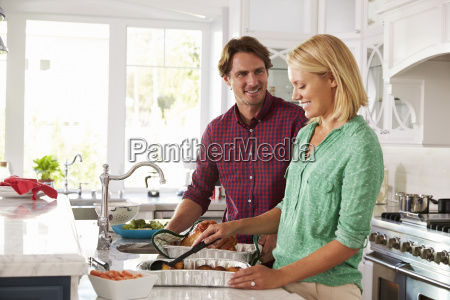 couple make roast turkey meal in