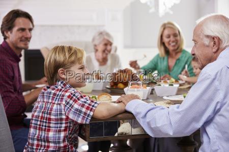 grossfamilie gruppe sitzen um tisch essen
