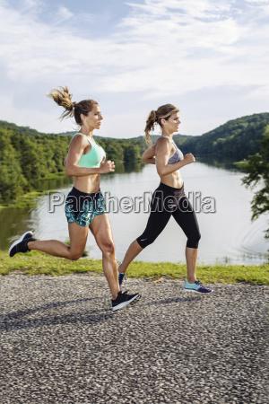 two athlete women jogging on street
