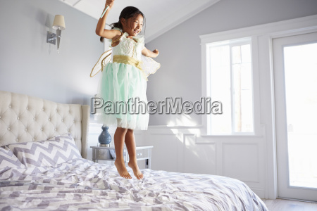 girl dressed in fairy costume jumping