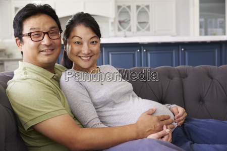 expectant couple relaxing on sofa at