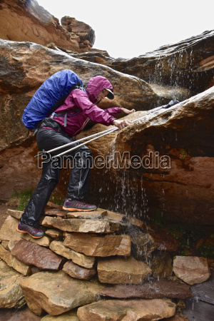 woman climbing rock navigating waterfall in