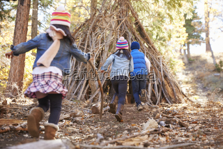 three kids play outside shelter made