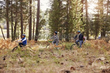 familie durch einen wald radfahren zusammen