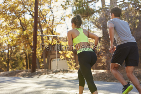 caucasian woman and man jogging on