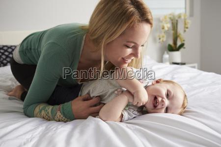 caucasian mother kneeling on bed tickling