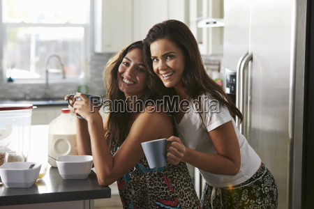 female couple embracing in the kitchen